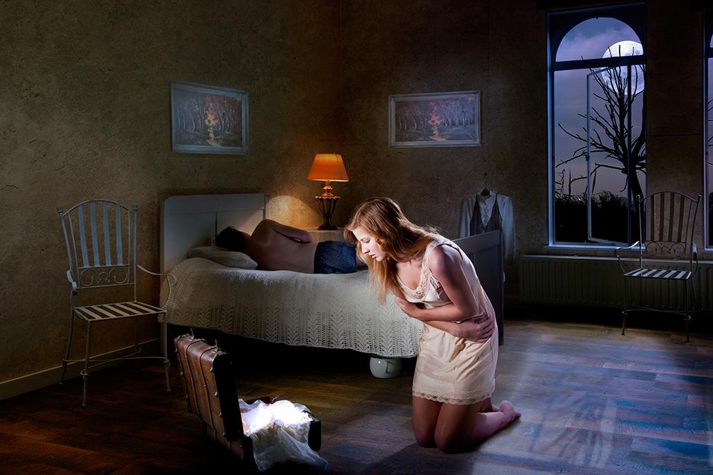 Vrouw knielend voor koffer, man liggend op bed. Berebeeld beeldmanipulatie voor Beeldkracht.